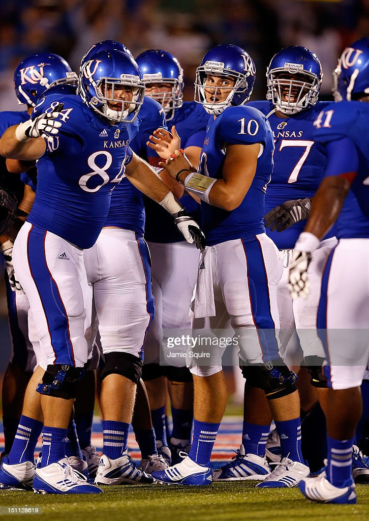 Quarterback Dayne Crist #10 of the Kansas Jayhawks celebrates with teammates after a touchdown during the game against the South Dakota State Jackrabbits at Memorial Stadium on September 1, 2012 in Lawrence, Kansas.