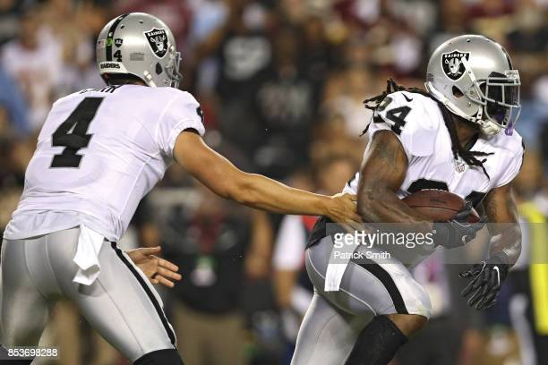 Quarterback Derek Carr hands off to running back Marshawn Lynch of the Oakland Raiders against the Washington Redskins during the first half at...