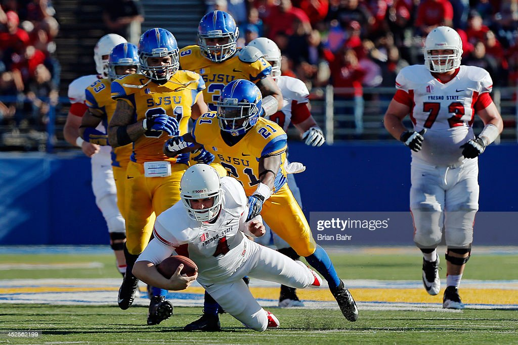 Quarterback Derek Carr of the Fresno State Bulldogs gets caught by cornerback Bene Benwikere of the San Jose State Spartans but picks up a first down...