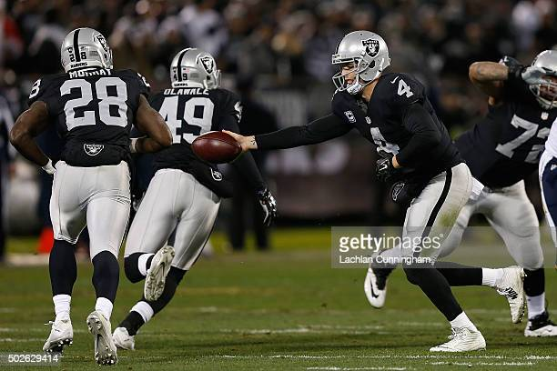 Quarterback Derek Carr of the Oakland Raiders hands the ball off to running back Latavius Murray in the first quarter against the San Diego Chargers...