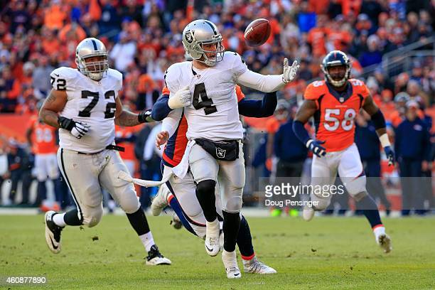 Quarterback Derek Carr of the Oakland Raiders is pressured by defensive end DeMarcus Ware of the Denver Broncos and loses control of the ball for a...
