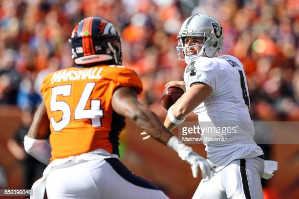 Quarterback Derek Carr of the Oakland Raiders looks to pass under pressure by inside linebacker Brandon Marshall of the Denver Broncos in the first...