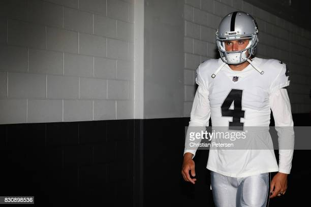 Quarterback Derek Carr of the Oakland Raiders walks out onto the field before the NFL game against the Arizona Cardinals at the University of Phoenix...