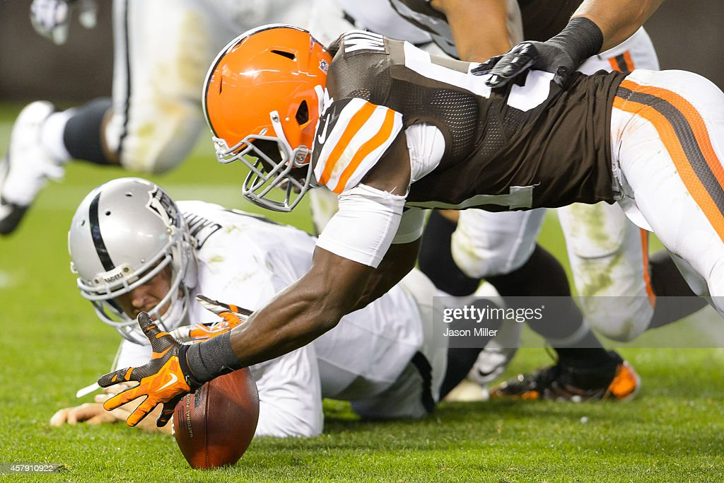 Quarterback Derek Carr of the Oakland Raiders watches as outside linebacker Barkevious Mingo of the Cleveland Browns recovers the fumble during the...