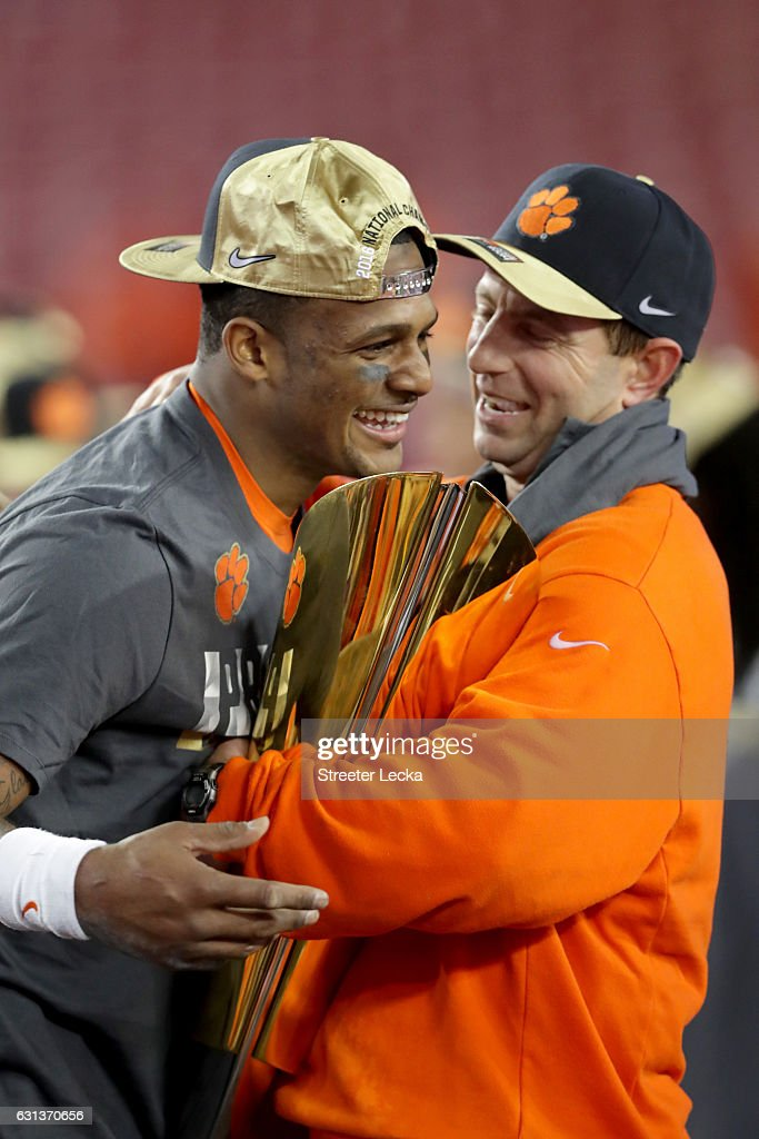 Quarterback Deshaun Watson #4 and head coach Dabo Swinney of the Clemson Tigers celebrate with the College Football Playoff National Championship Trophy after defeating the Alabama Crimson Tide 35-31 to win the 2017 College Football Playoff National Championship Game at Raymond James Stadium on January 9, 2017 in Tampa, Florida.