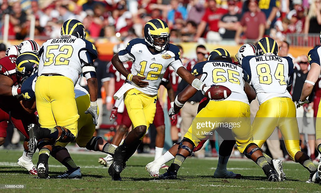 Quarterback Devin Gardner #12 of the Michigan Wolverines hands the ball off against the South Carolina Gamecocks during the Outback Bowl Game at Raymond James Stadium on January 1, 2013 in Tampa, Florida.