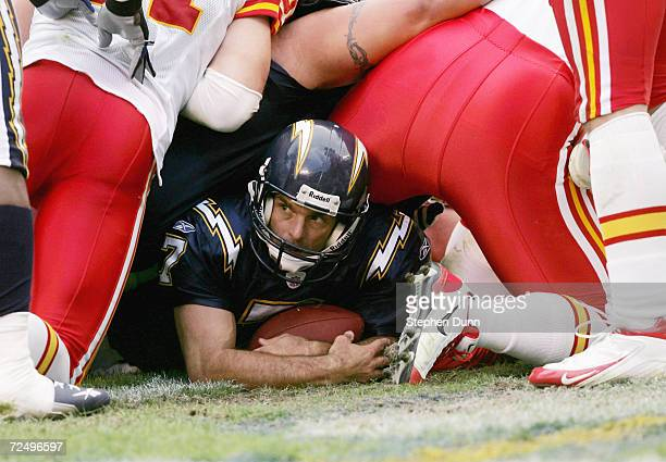 Quarterback Doug Flutie of the San Diego Chargers cradles the ball in the end zone under a pile of players after scoring a touchdown on a quarterback...