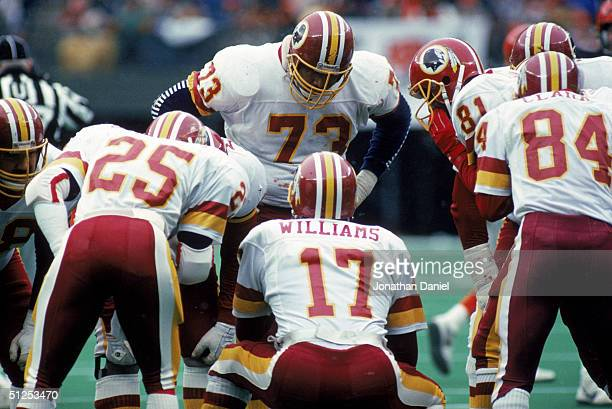 Quarterback Doug Williams of the Washington Redskins calls a play in the huddle during a game against the Cincinnati Bengals at Riverfront Stadium on...