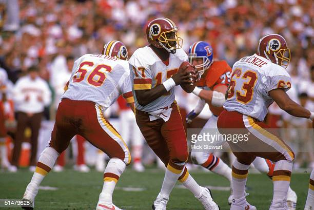 Quarterback Doug Williams of the Washington Redskins drops back to pass during Super Bowl XXII against the Denver Broncos at Jack Murphy Stadium on...