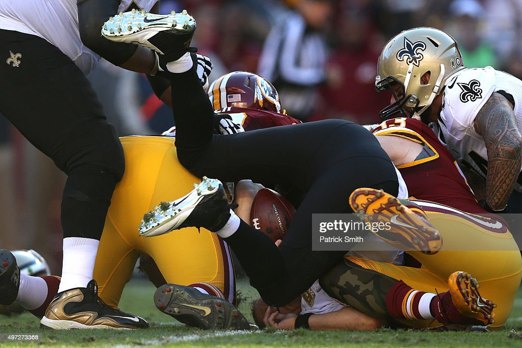 Quarterback Drew Brees of the New Orleans Saints is sacked by outside linebacker Trent Murphy and Chris Baker of the Washington Redskins in the...