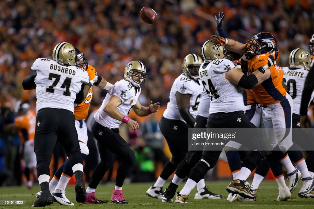 Quarterback Drew Brees #9 of the New Orleans Saints looses control of the football while trying to make a pass during the first half against the Denver Broncos at Sports Authority Field Field at Mile High on October 28, 2012 in Denver, Colorado. New Orleans recovered the ball but the Broncos defeated the Saints 34-14.