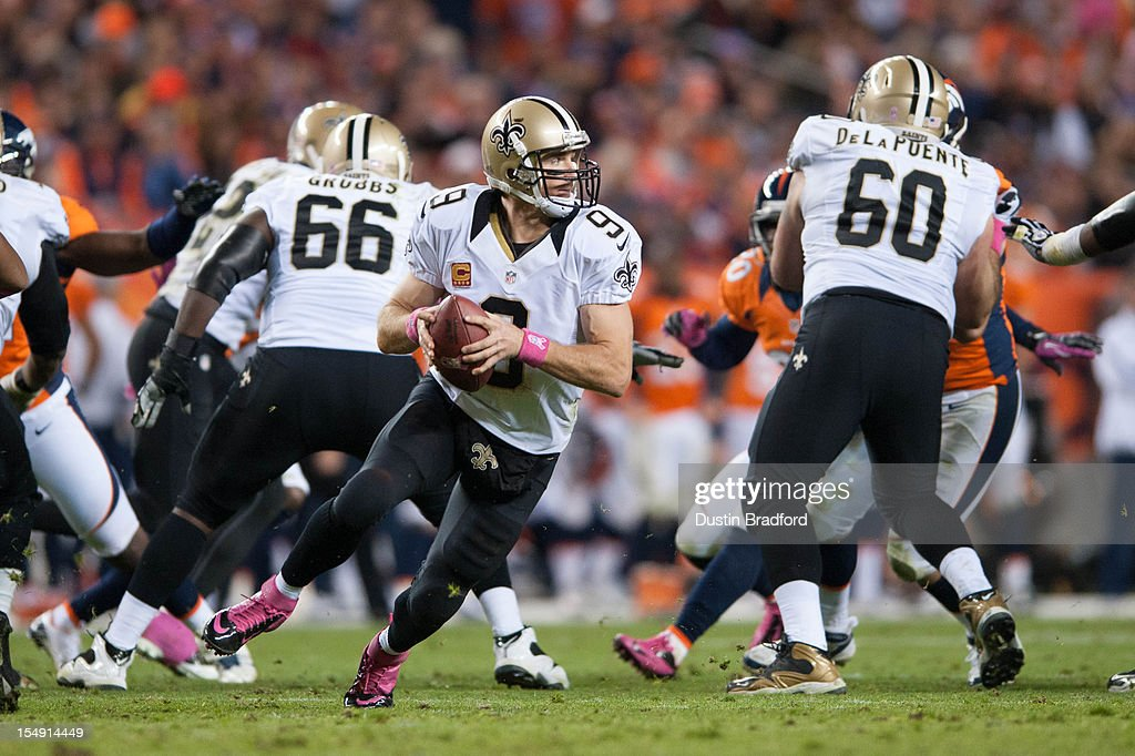 Quarterback <a gi-track='captionPersonalityLinkClicked' href=/galleries/search?phrase=Drew+Brees&family=editorial&specificpeople=202562 ng-click='$event.stopPropagation()'>Drew Brees</a> #9 of the New Orleans Saints scrambles out of the pocket during a game against the Denver Broncos at Sports Authority Field Field at Mile High on October 28, 2012 in Denver, Colorado.