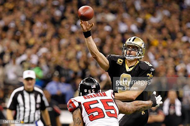 Quarterback Drew Brees of the New Orleans Saints throws the ball as defensive end John Abraham of the Atlanta Falcons rushes in during the second...