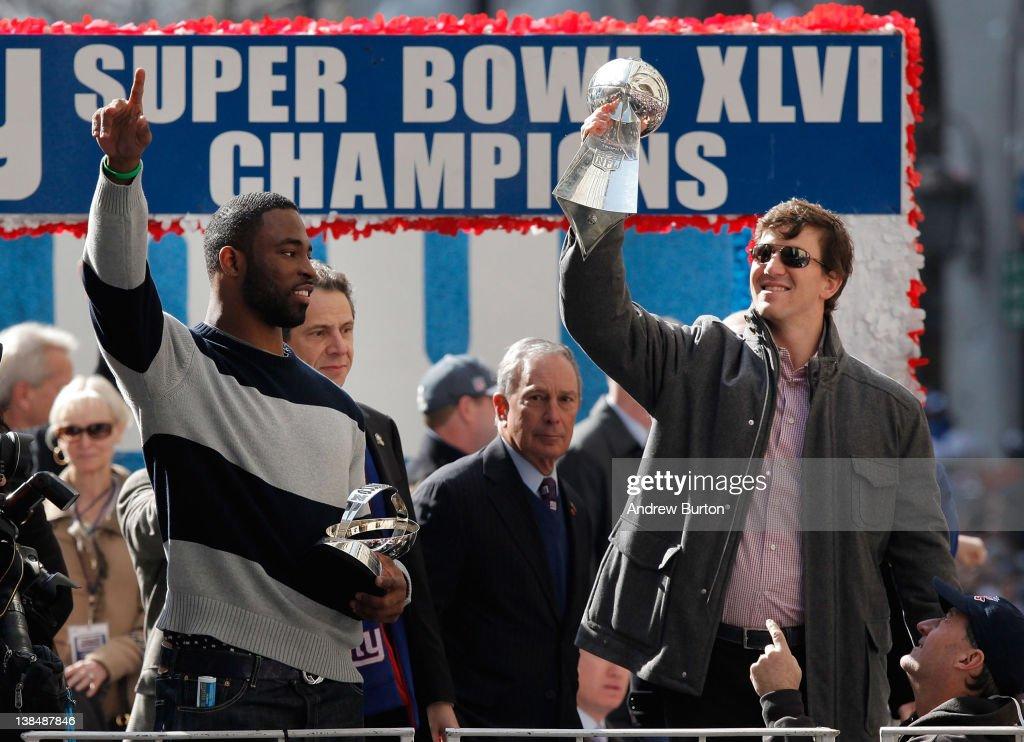 Quarterback Eli Manning of the New York Giants and Super Bowl XLVI MVP holds the Vince Lombardi Trophy as Justin Tuck of the New York Giants looks on...