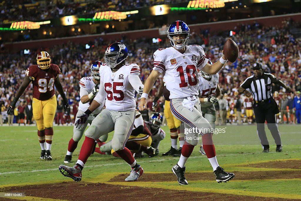 Quarterback <a gi-track='captionPersonalityLinkClicked' href=/galleries/search?phrase=Eli+Manning&family=editorial&specificpeople=202013 ng-click='$event.stopPropagation()'>Eli Manning</a> #10 of the New York Giants celebrates his 4th quarter touchdown against the Washington Redskins at FedExField on September 25, 2014 in Landover, Maryland.