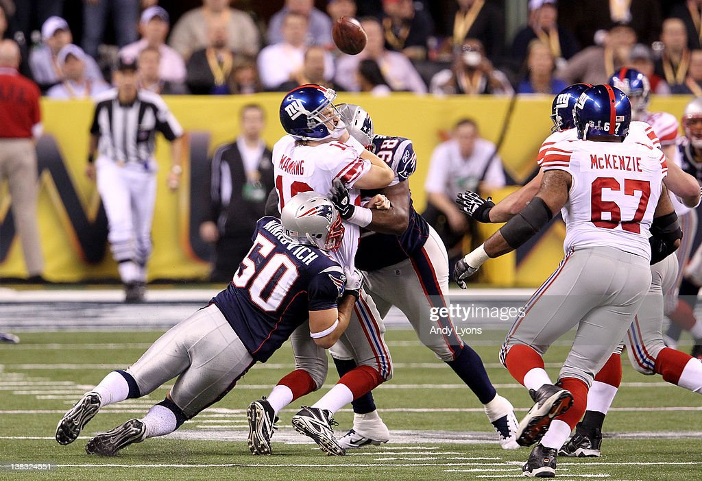Quarterback Eli Manning of the New York Giants gets sack in the third quarter by Rob Ninkovich and Gerard Warren of the New England Patriots during...