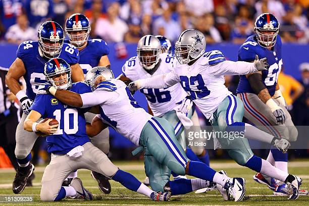 Quarterback Eli Manning of the New York Giants gets sacked by defensive end Jason Hatcher of the Dallas Cowboys during the 2012 NFL season opener at...