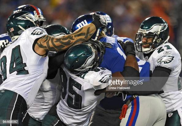 Quarterback Eli Manning of the New York Giants gets sakced by defensive end Jason Babin defensive end Victor Abiamiri and cornerback Joselio Hanson...
