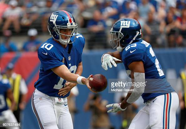Quarterback Eli Manning of the New York Giants hands off to Rashad Jennings against the New Orleans Saints during the first quarter at MetLife...