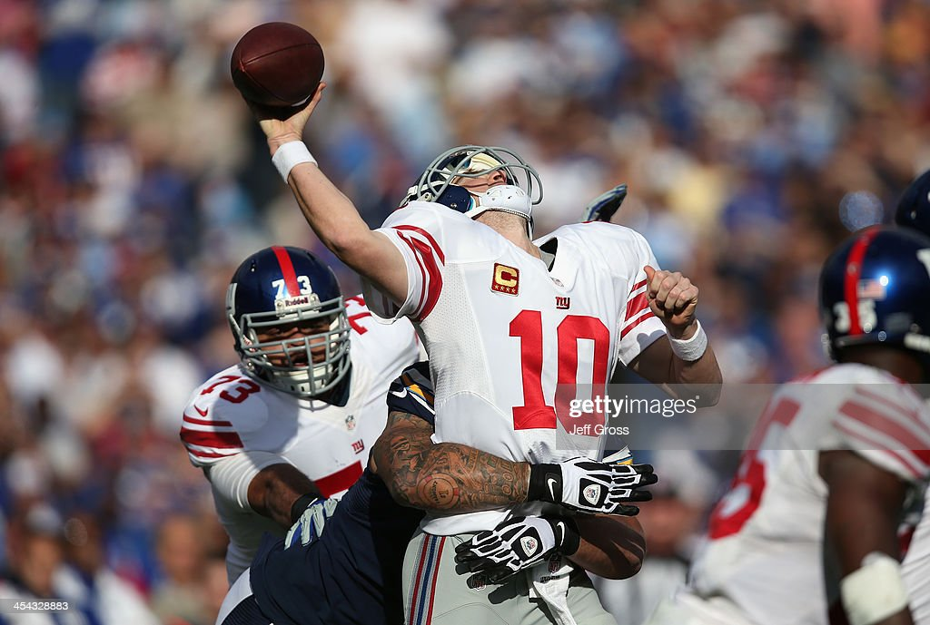 Quarterback Eli Manning of the New York Giants is hit by defensive tackle Lawrence Guy of the San Diego Chargers in the first half at Qualcomm...