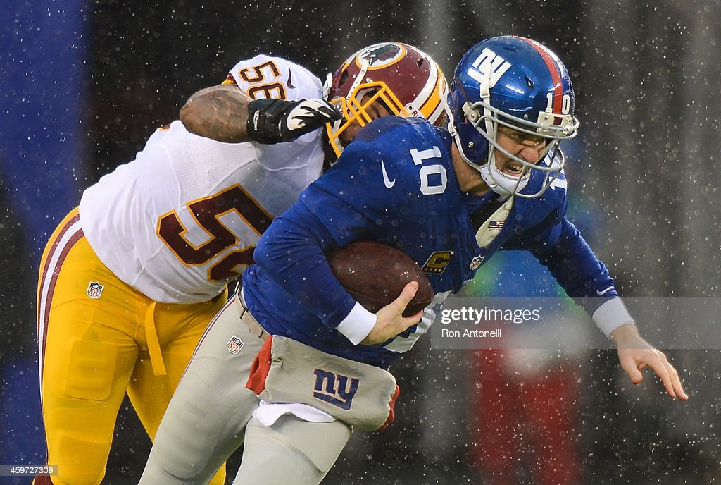 Quarterback Eli Manning of the New York Giants is sacked by inside linebacker Perry Riley of the Washington Redskins in the first half at MetLife...