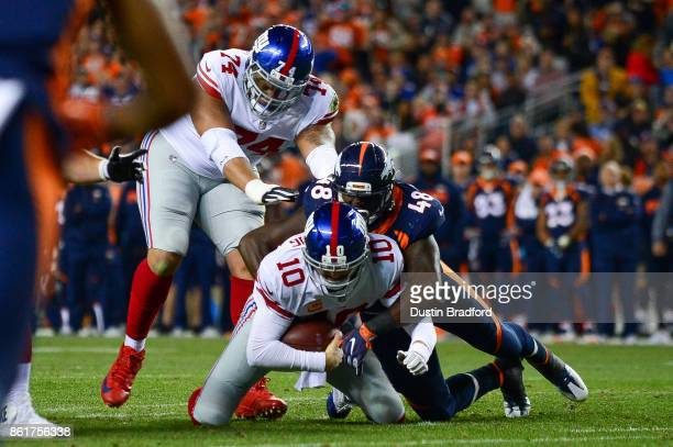 Quarterback Eli Manning of the New York Giants is sacked by outside linebacker Shaquil Barrett of the Denver Broncos in the red zone on third down in...