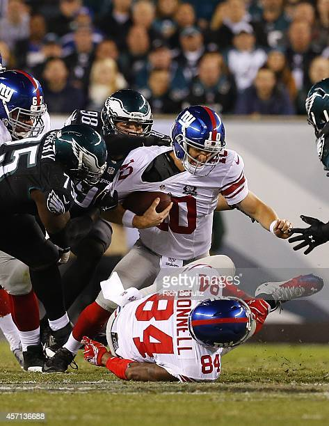Quarterback Eli Manning of the New York Giants is sacked by Vinny Curry and Connor Barwin of the Philadelphia Eagles during the second quarter in a...