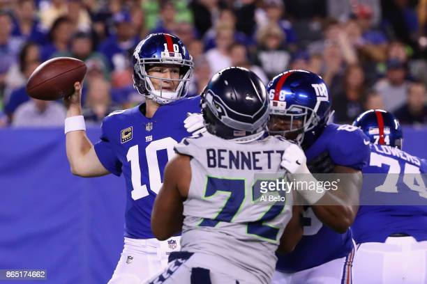 Quarterback Eli Manning of the New York Giants looks to pass against Michael Bennett of the Seattle Seahawks during the second half of the game at...