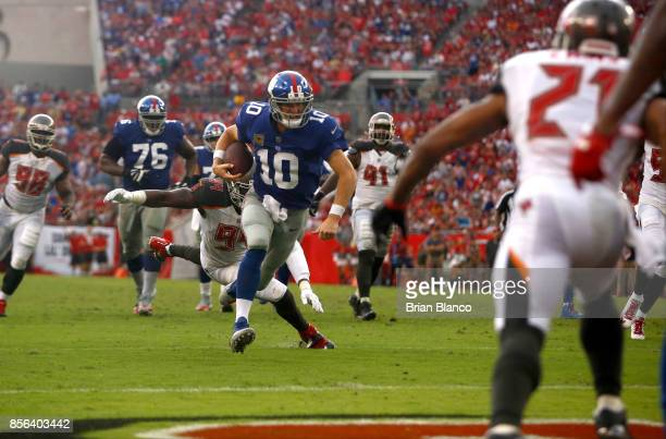 Quarterback Eli Manning of the New York Giants rushes for a 14yard touchdown while evading defensive end Will Clarke of the Tampa Bay Buccaneers...