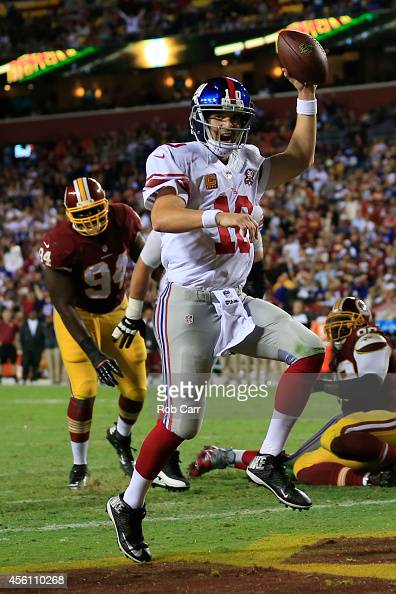 Quarterback Eli Manning of the New York Giants scores a fourth quarter touchdown against the Washington Redskins at FedExField on September 25 2014...