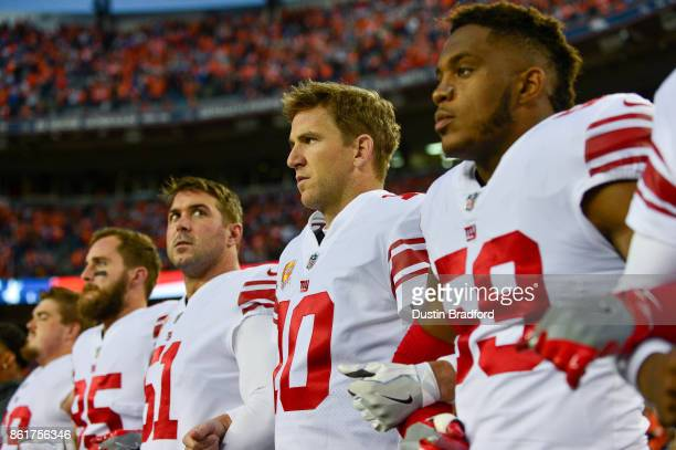 Quarterback Eli Manning of the New York Giants stands with his and teammates' arms locked during the national anthem before a game against the Denver...