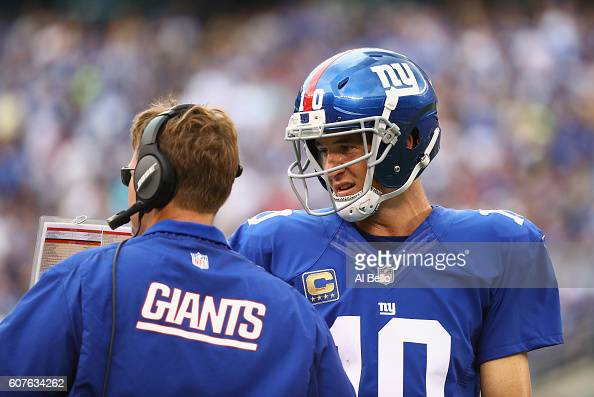 Quarterback Eli Manning of the New York Giants talks with head coach Ben McAdoo against the New Orleans Saints during the second half at MetLife...