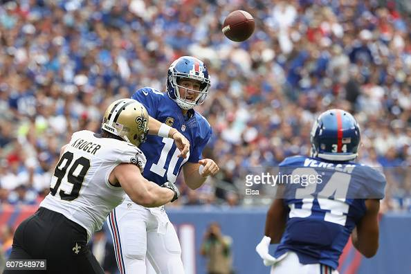 Quarterback Eli Manning of the New York Giants throws a pass to teammate Shane Vereen against Paul Kruger of the New Orleans Saints during the first...