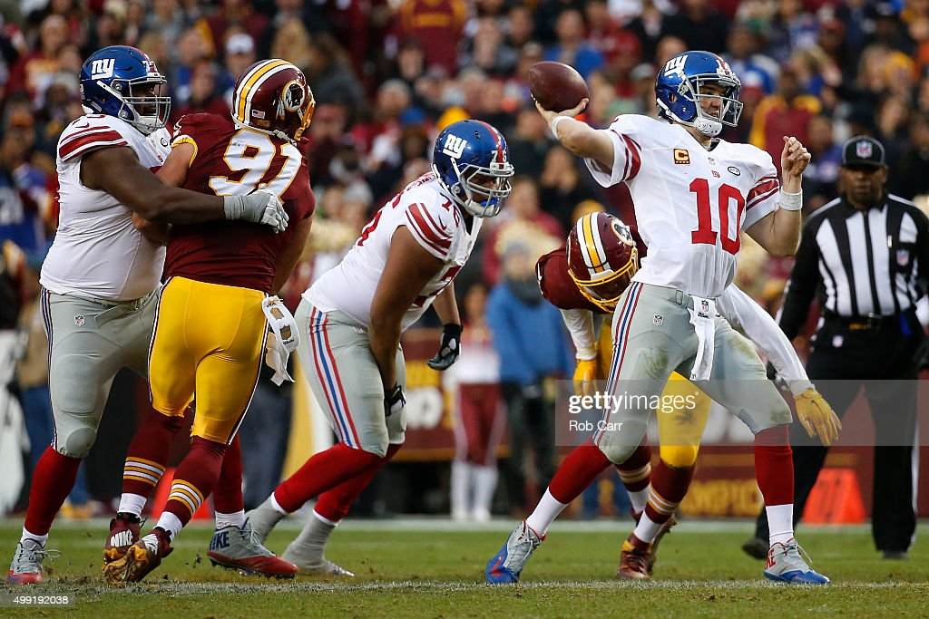 Quarterback Eli Manning #10 of the New York Giants throws the ball while offensive tackle Marshall Newhouse #73 of the New York Giants blocks outside linebacker Ryan Kerrigan #91 of the Washington Redskins in the fourth quarter at FedExField on November 29, 2015 in Landover, Maryland.