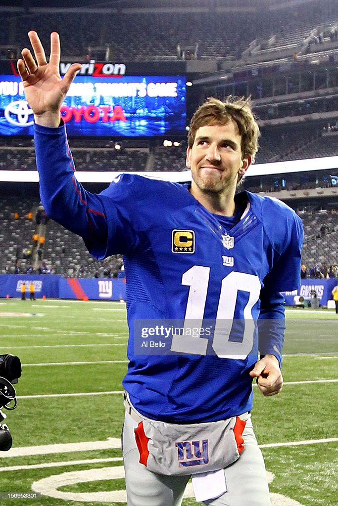 Quarterback <a gi-track='captionPersonalityLinkClicked' href=/galleries/search?phrase=Eli+Manning&family=editorial&specificpeople=202013 ng-click='$event.stopPropagation()'>Eli Manning</a> #10 of the New York Giants waves as he runs of the field after defeating the Green Bay Packers by a score of 38-10 at MetLife Stadium on November 25, 2012 in East Rutherford, New Jersey.