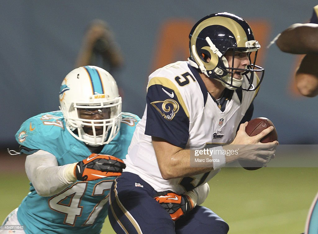 Quarterback <a gi-track='captionPersonalityLinkClicked' href=/galleries/search?phrase=Garrett+Gilbert&family=editorial&specificpeople=5652883 ng-click='$event.stopPropagation()'>Garrett Gilbert</a> #5 of the St. Louis Rams tries to evade <a gi-track='captionPersonalityLinkClicked' href=/galleries/search?phrase=Chris+McCain&family=editorial&specificpeople=8222562 ng-click='$event.stopPropagation()'>Chris McCain</a> #47 of the Miami Dolphins in the fourth quarter at Sun Life Stadium on August 28, 2014 in Miami Gardens, Florida.