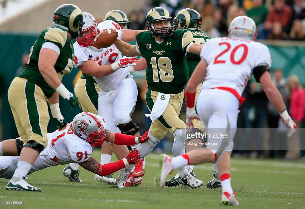 quarterback Garrett Grayson of the Colorado State Rams eludes defensive lineman Nik D'Avanzo of the New Mexico Lobos and delivers a pass on November...