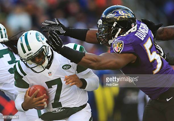 Quarterback Geno Smith of the New York Jets is hit by outside linebacker Elvis Dumervil of the Baltimore Ravens during the first half at MT Bank...