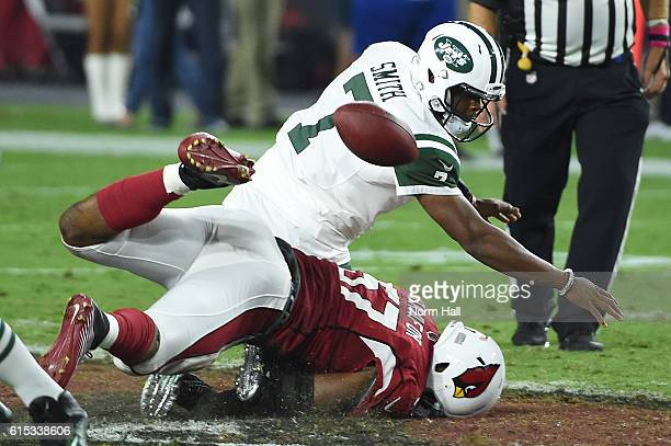 Quarterback Geno Smith of the New York Jets is sacked by outside linebacker Alex Okafor of the Arizona Cardinals during the fourth quarter of the NFL...