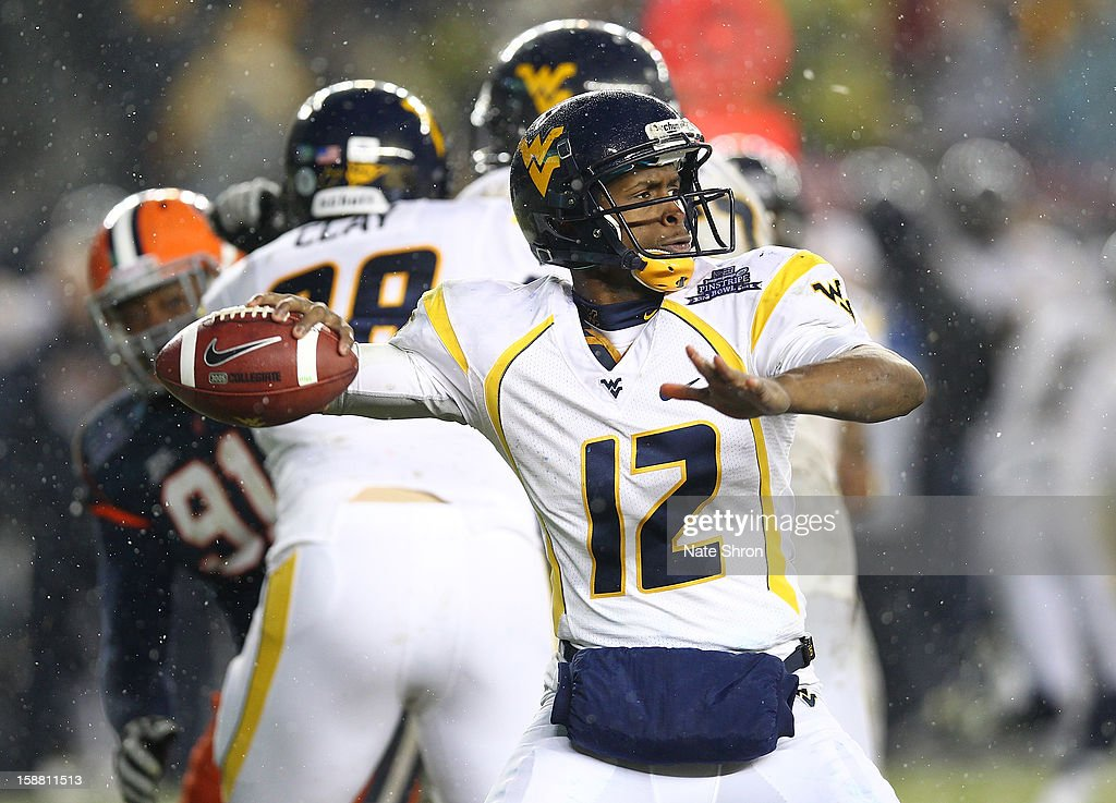 Quarterback Geno Smith #12 of the West Virginia Mountaineers passes the ball against the Syracuse Orange during the New Era Pinstripe Bowl at Yankee Stadium on December 29, 2012 in the Bronx borough of New York City.