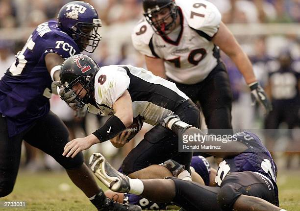 Quarterback Gino Guidugli of the Cincinnati Bearcats is sacked by Ranorris Ray and Maurice Bouldwin of the Texas Christian University Horned Frogs on...