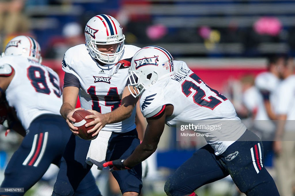 Quarterback Graham Wilbert #14 of the Florida Atlantic Owls prepares to hand the ball off to running back <a gi-track='captionPersonalityLinkClicked' href=/galleries/search?phrase=Jonathan+Wallace+-+American+Football+Quarterback&family=editorial&specificpeople=15195972 ng-click='$event.stopPropagation()'>Jonathan Wallace</a> #27 of the Florida Atlantic Owls on October 20, 2012 at Ladd-Peebles Stadium in Mobile, Alabama. South Alabama defeated Florida Atlantic in the second overtime 37-34.