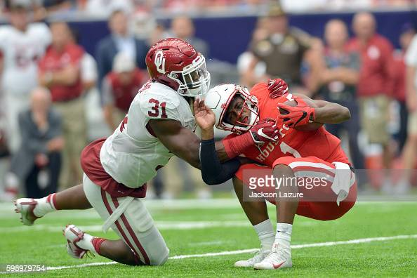 Quarterback Greg Ward Jr #1 of the Houston Cougars is tackled by linebacker Ogbonnia Okoronkwo the Oklahoma Sooners on Saturday September 3 2016 at...