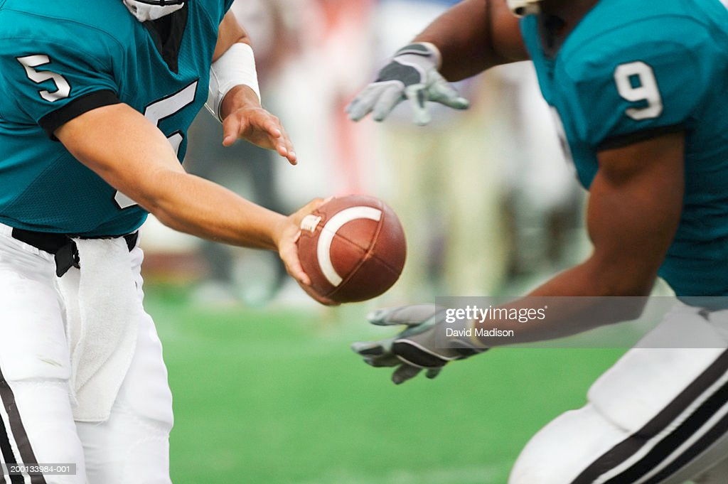 Quarterback handing off football to running back, mid section : Stock Photo