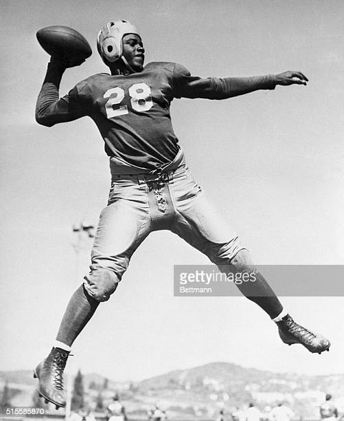 UCLA quarterback Jackie Robinson the college's first studentathlete to earn varsity letters in four different sports leaps in the air to throw a pass...