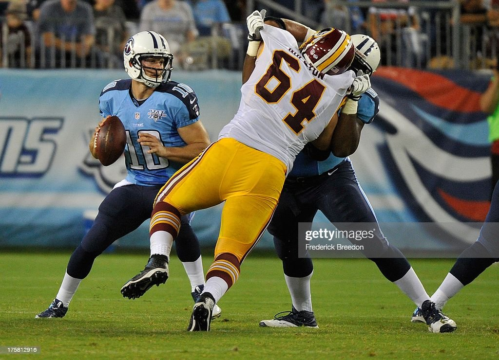 Quarterback <a gi-track='captionPersonalityLinkClicked' href=/galleries/search?phrase=Jake+Locker&family=editorial&specificpeople=4450185 ng-click='$event.stopPropagation()'>Jake Locker</a> #10 of the Tennessee Titans drops back in the pocket behind Kedric Golston #64 of the Washington Redskins during a pre-season game at LP Field on August 8, 2013 in Nashville, Tennessee.