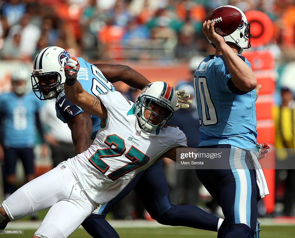 Quarterback <a gi-track='captionPersonalityLinkClicked' href=/galleries/search?phrase=Jake+Locker&family=editorial&specificpeople=4450185 ng-click='$event.stopPropagation()'>Jake Locker</a> #10 of the Tennessee Titans is sacked by Jimmy Wilson #27 of the Miami Dolphins at Sun Life Stadium on November 11, 2012 in Miami Gardens, Florida.