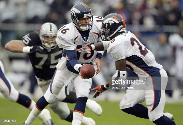 Quarterback Jake Plummer of the Denver Broncos hands off to Clinton Portis during the game against the Oakland Raiders on November 30 2003 at Network...