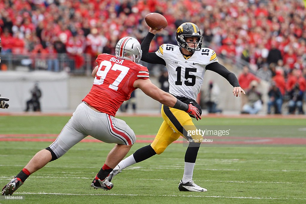 Quarterback Jake Rudock #15 of the Iowa Hawkeyes passes in the second quarter as Joey Bosa #97 of the Ohio State Buckeyes applies pressure at Ohio Stadium on October 19, 2013 in Columbus, Ohio. Ohio State defeated Iowa 34-24.