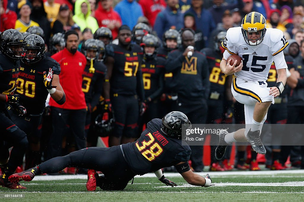 Quarterback Jake Rudock of the Michigan Wolverines eludes the tackle of Brett Zanotto of the Maryland Terrapins during the first half at Byrd Stadium...